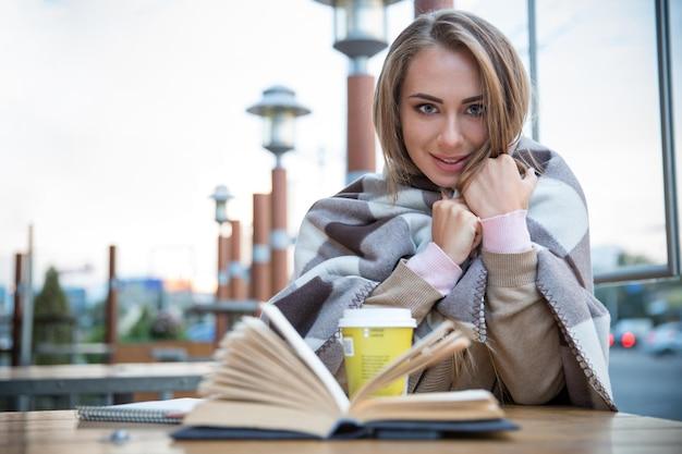 Portret van een gelukkige vrouwelijke student zittend met boek en koffie in café sitting