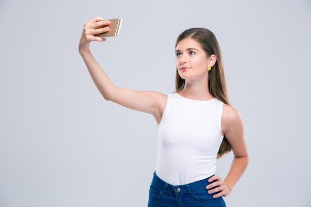 Portret van een gelukkige vrouwelijke tiener die selfiefoto op geïsoleerde smartphone maakt