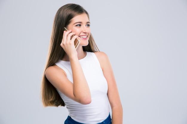 Portret van een gelukkige vrouwelijke tiener praten aan de telefoon geïsoleerd