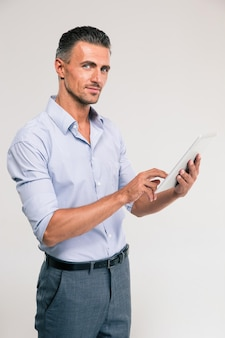 Portret van een gelukkige zakenman die geïsoleerde tabletcomputer met behulp van