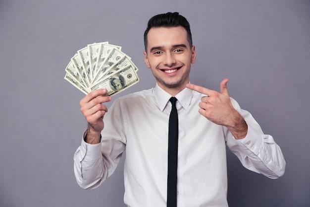 Portret van een gelukkige zakenman die geld aanhoudt dat op een witte muur wordt geïsoleerd