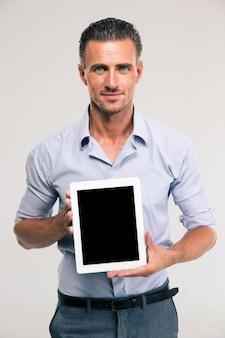 Portret van een gelukkige zakenman die het lege geïsoleerde scherm van de tabletcomputer toont