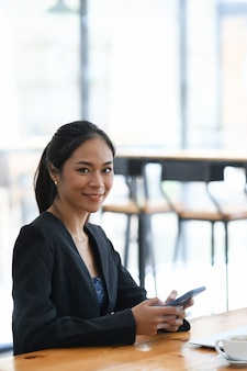 Portret van een gelukkige zakenvrouw die een mobiele telefoon vasthoudt en naar de camera glimlacht terwijl ze in een modern kantoor zit.
