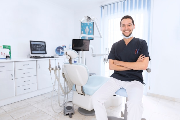 Portret van een gelukkige zekere tandarts in kliniek
