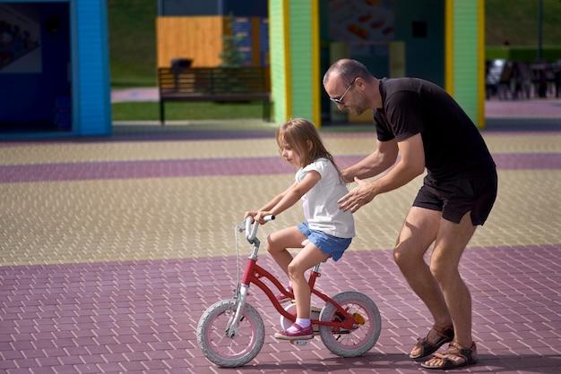 Portret van een gelukkige zorgzame vader die zijn kleine mooie dochter onderwijst die een fiets in een groen park berijdt, die volledige lengte glimlacht