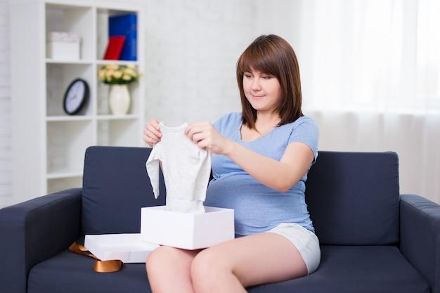 Portret van een gelukkige zwangere vrouw die een geschenkdoos opent voor de baby