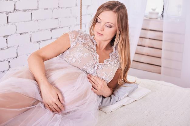 Portret van een gelukkige zwangere vrouw thuis gekleed in een witte kleding
