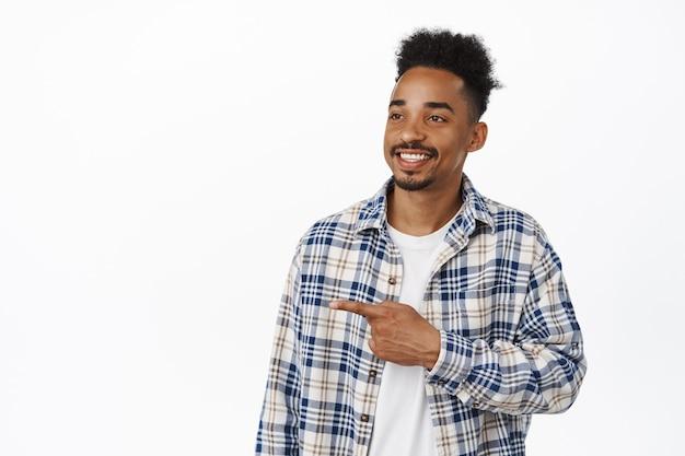 Portret van een gelukkige zwarte man, jonge 20s bebaarde man die tevreden glimlacht, met de vinger naar links wijst en naar de verkoopbanner kijkt, met het logo opzij op wit. ruimte kopiëren