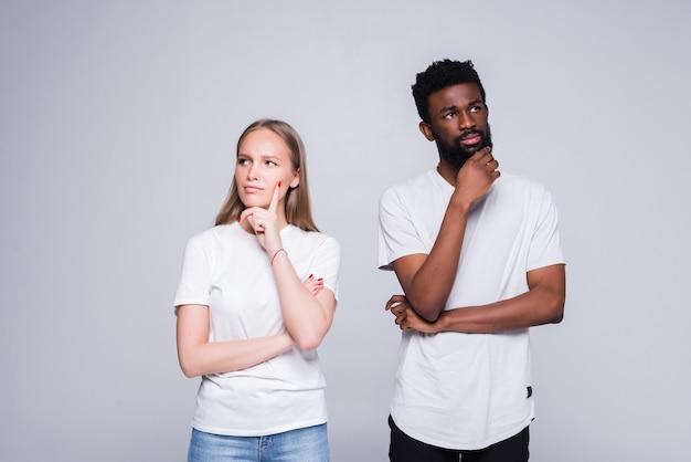 Portret van een gemengd raspaar dat denkt en zich zorgen maakt over hun relatie op een witte muur