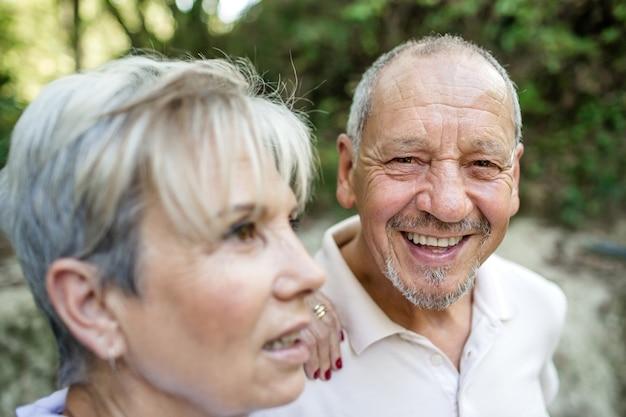 Portret van een gepensioneerd echtpaar waar de man lacht kijkend naar de camera tijdens een wandeling in het bos bij zonsondergang.