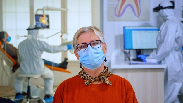 Portret van een gepensioneerde patiënt in een tandartspraktijk die op de camera kijkt met een gezichtsmasker op een stoel in de wachtkamerkliniek terwijl de arts aan het werk is. concept van nieuw normaal tandartsbezoek in coronavirus outbre