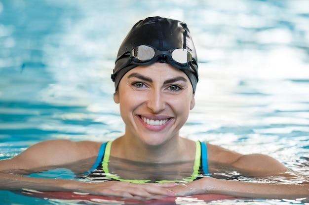 Portret van een geschikte jonge vrouw die een zwemmuts en een veiligheidsbril draagt in het zwembad
