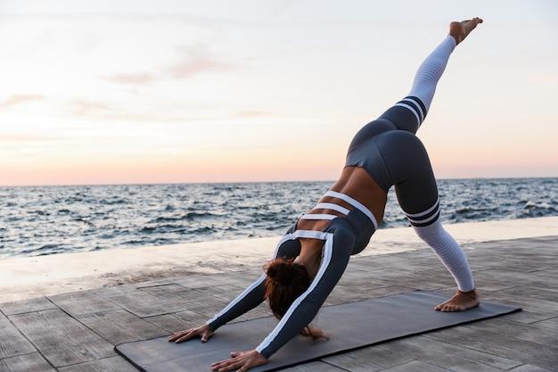 Portret van een geschikte jonge vrouw die yogaoefeningen doet
