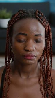 Portret van een geschikte zwarte vrouw die in de lotuspositie zit en de lichaamsspieren uitrekt