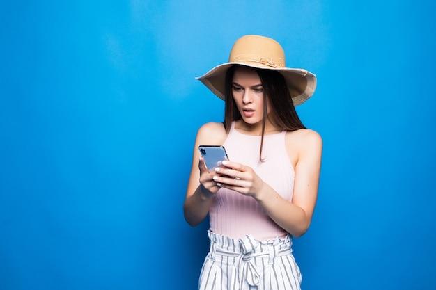 Portret van een geschokt jonge vrouw die in de zomerhoed mobiele telefoon bekijkt die over blauwe muur wordt geïsoleerd.