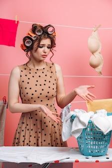 Portret van een geschokt meisje dat naar een mand met kleren wijst. huisvrouw met krulspelden op haar haar op een roze achtergrond. Premium Foto