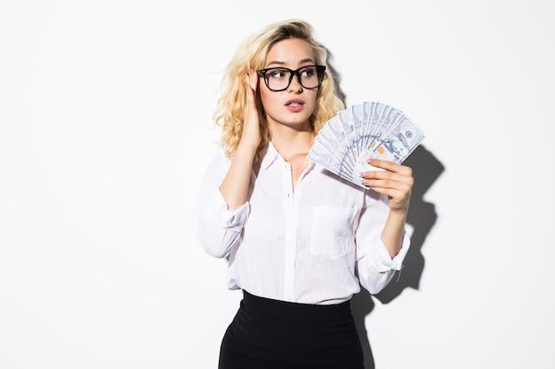 Portret van een geschokt mooi meisje dat een bos geldbankbiljetten houdt en haar mond bedekt die over witte muur wordt geïsoleerd