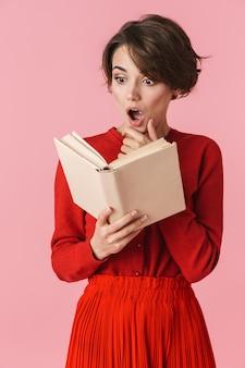 Portret van een geschokt mooie jonge vrouw, gekleed in een rode jurk staande geïsoleerd, een boek lezen