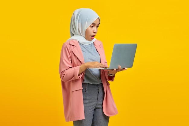 Portret van een geschokt verrast meisje dat een laptopcomputer vasthoudt die over een blauwe achtergrond wordt geïsoleerd
