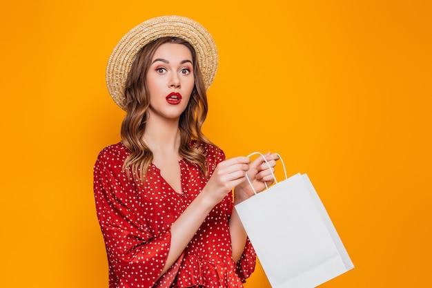 Portret van een geschokt verrast meisje gekleed in een rode jurk en strooien hoed met rode lippen met boodschappentassen en kijken naar camera geïsoleerd over oranje muur