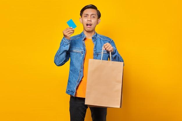 Portret van een geschokte aziatische man met een creditcard en een boodschappentas op een gele achtergrond