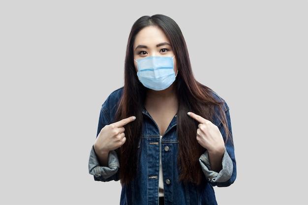 Portret van een geschokte brunette aziatische jonge vrouw met een chirurgisch medisch masker in een blauw spijkerjasje dat zichzelf wijst en naar de camera kijkt. indoor studio opname, geïsoleerd op een grijze achtergrond.