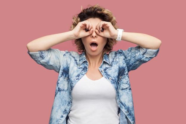 Portret van een geschokte grappige jonge vrouw met krullend haar in een blauw shirt met een verrekijker gebaar handen op het oog en kijkend naar de camera met een verbaasd gezicht. indoor studio-opname geïsoleerd op roze achtergrond