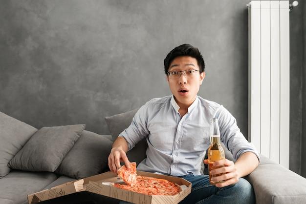 Portret van een geschokte jonge aziatische mens die pizza eet