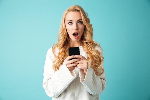Portret van een geschokte jonge blonde vrouw in trui