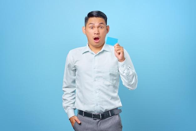 Portret van een geschokte jonge knappe zakenman die een creditcard in hand op blauwe achtergrond houdt