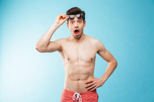 Portret van een geschokte jonge man in zwemshort