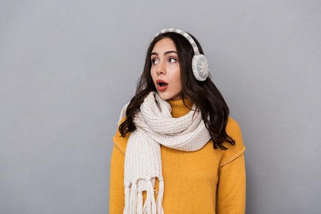 Portret van een geschokte jonge vrouw die sweater en sjaal draagt die over grijze achtergrond wordt geïsoleerd