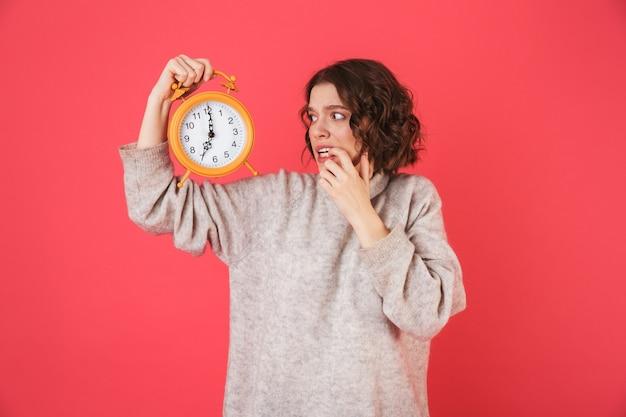 Portret van een geschokte jonge vrouw die zich geïsoleerd over roze bevindt, die wekker toont