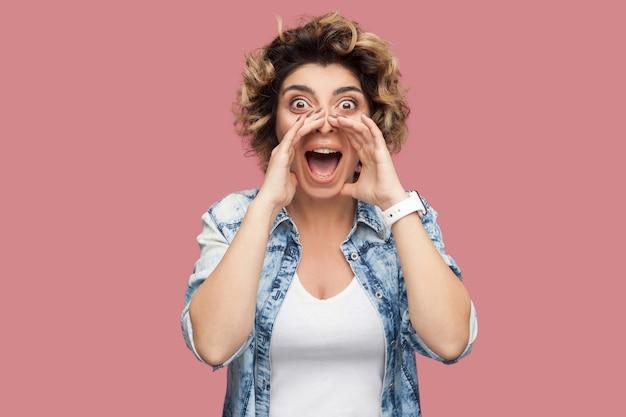 Portret van een geschokte jonge vrouw met krullend kapsel in een casual blauw shirt dat staat, schreeuwt, iets deelt en naar de camera kijkt met een verbaasd gezicht. indoor studio-opname, geïsoleerd op roze achtergrond