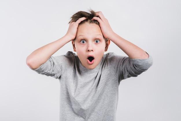 Portret van een geschokte jongen met zijn handen op hoofd die aan camera tegen grijze achtergrond kijken