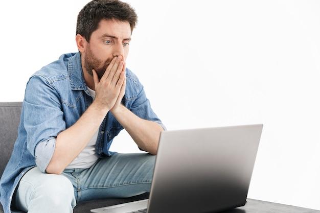 Portret van een geschokte knappe bebaarde man met vrijetijdskleding zittend in een stoel geïsoleerd, werkend op een laptopcomputer