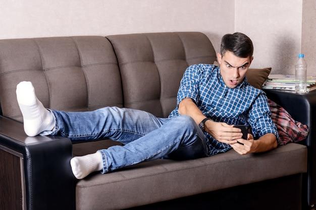 Portret van een geschokte man, wakker op de bank thuis en kijkend op een smartphone, verslapen voor het werk