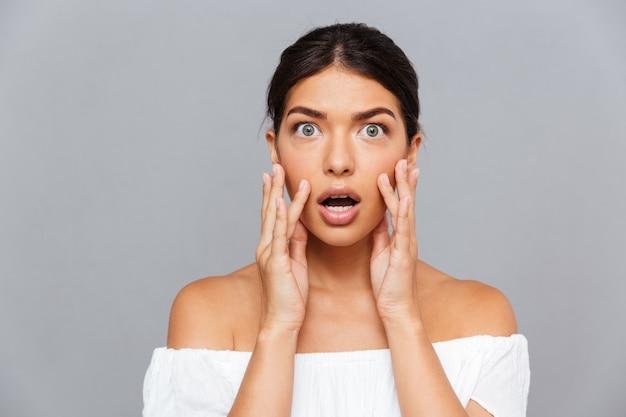 Portret van een geschokte mooie jonge vrouw die haar gezicht aanraakt over een grijze muur