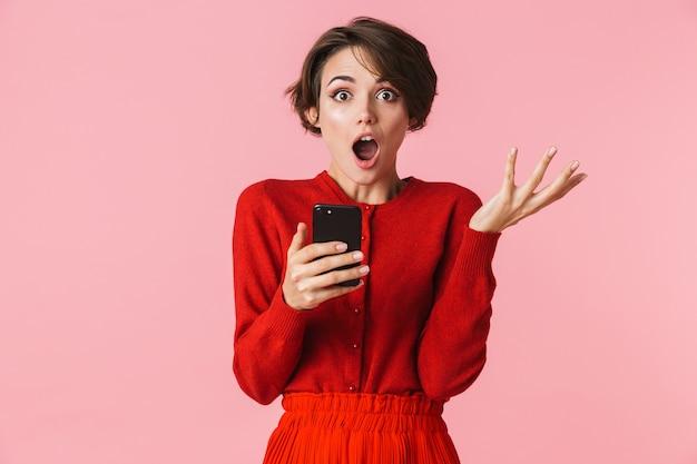 Portret van een geschokte mooie jonge vrouw die rode kleren draagt die zich geïsoleerd bevinden, met mobiele telefoon