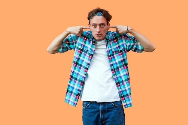 Portret van een geschokte of verwarde jongeman in een casual blauw geruit overhemd en een hoofdband die staat, de vinger op zijn oren legt en naar de camera kijkt. indoor studio opname, geïsoleerd op een oranje achtergrond.