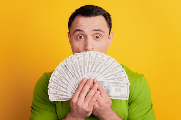 Portret van een geschokte rijke man die een geldventilator vasthoudt op de mond op gele achtergrond