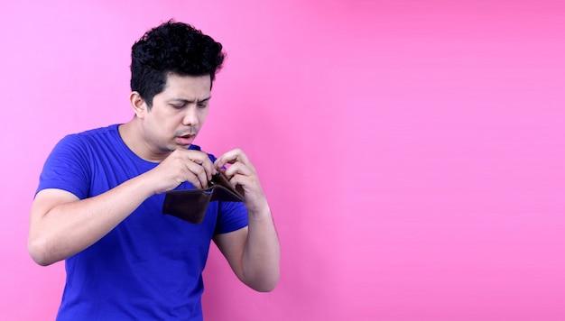 Portret van een geschokte, verbaasde sprakeloze man azië, met een lege portemonnee op roze achtergrond in de studio