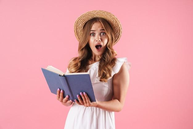 Portret van een geschokte verwarde schattige jonge mooie vrouw die zich voordeed over een roze muurleesboek. camera kijken.