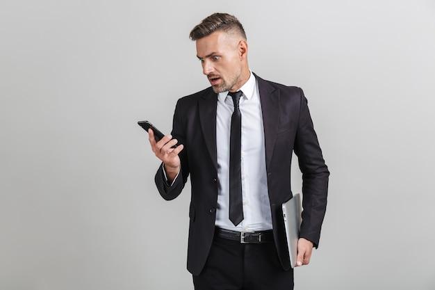Portret van een geschokte volwassen zakenman in een kantoorpak die naar een smartphone kijkt en een laptop vasthoudt terwijl hij geïsoleerd staat