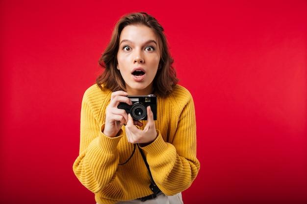 Portret van een geschokte vrouw die uitstekende camera houdt