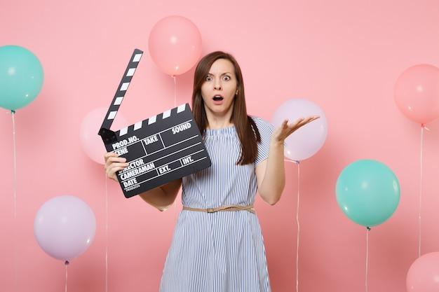 Portret van een geschokte vrouw in blauwe jurk die handen uitspreidt met klassieke zwarte film filmklapper op roze achtergrond met kleurrijke luchtballonnen. verjaardagsfeestje, oprechte emoties van mensen.