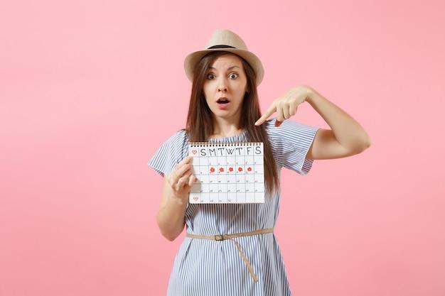 Portret van een geschokte vrouw in blauwe jurk, hoed met periodenkalender voor het controleren van menstruatiedagen geïsoleerd op een heldere trending roze achtergrond. medisch, gezondheidszorg, gynaecologisch concept. ruimte kopiëren