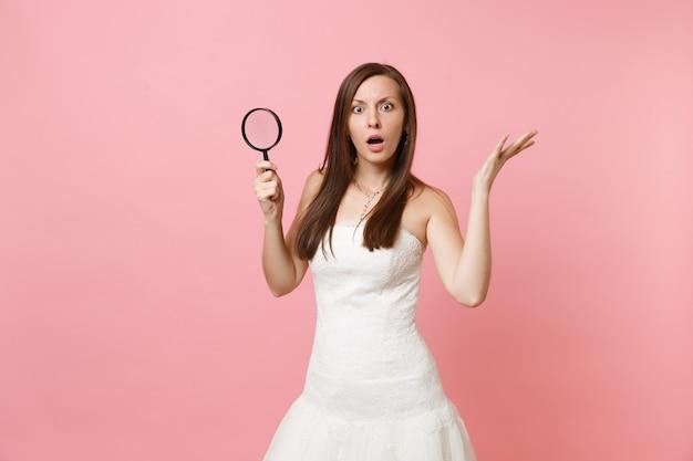 Portret van een geschokte vrouw in witte kanten jurk die handen uitspreidt, vergrootglas vasthoudt