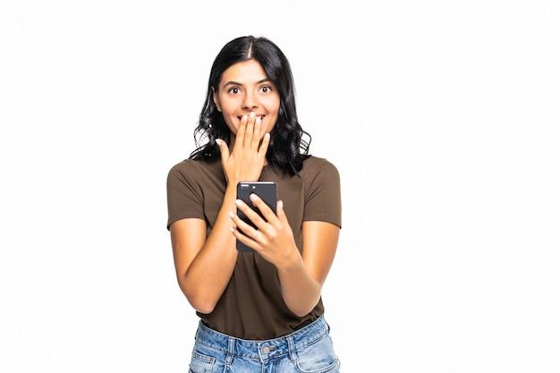 Portret van een geschokte zakenvrouw die mobiele telefoon gebruikt die over witte muur wordt geïsoleerd