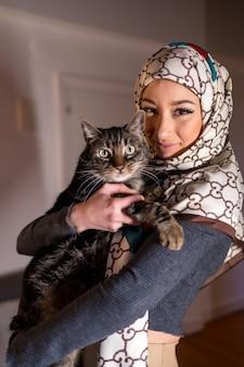 Portret van een gesluierde jonge vrouw met een mooie kat thuis